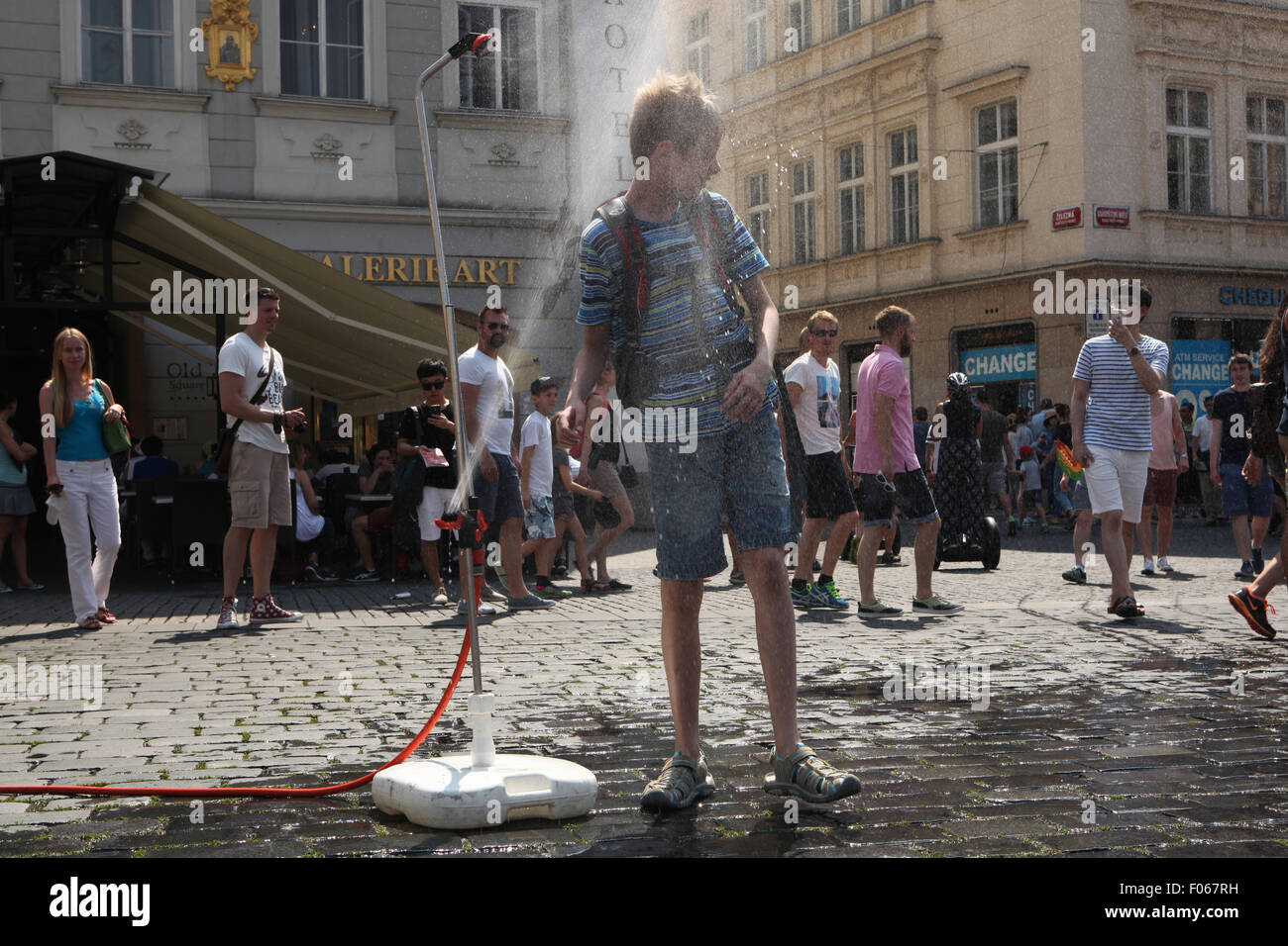 Prague, Czech Republic. 7th August 2015. A boy tries to cool off from a water sprinkler installed in Old Town Square - Stock Image