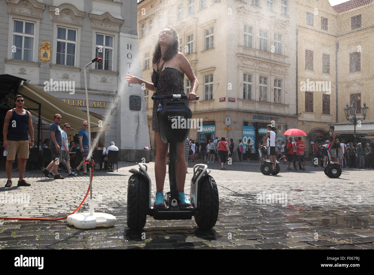 Prague, Czech Republic. 7th August 2015. A young woman riding a Segway tries to cool off from a water sprinkler - Stock Image
