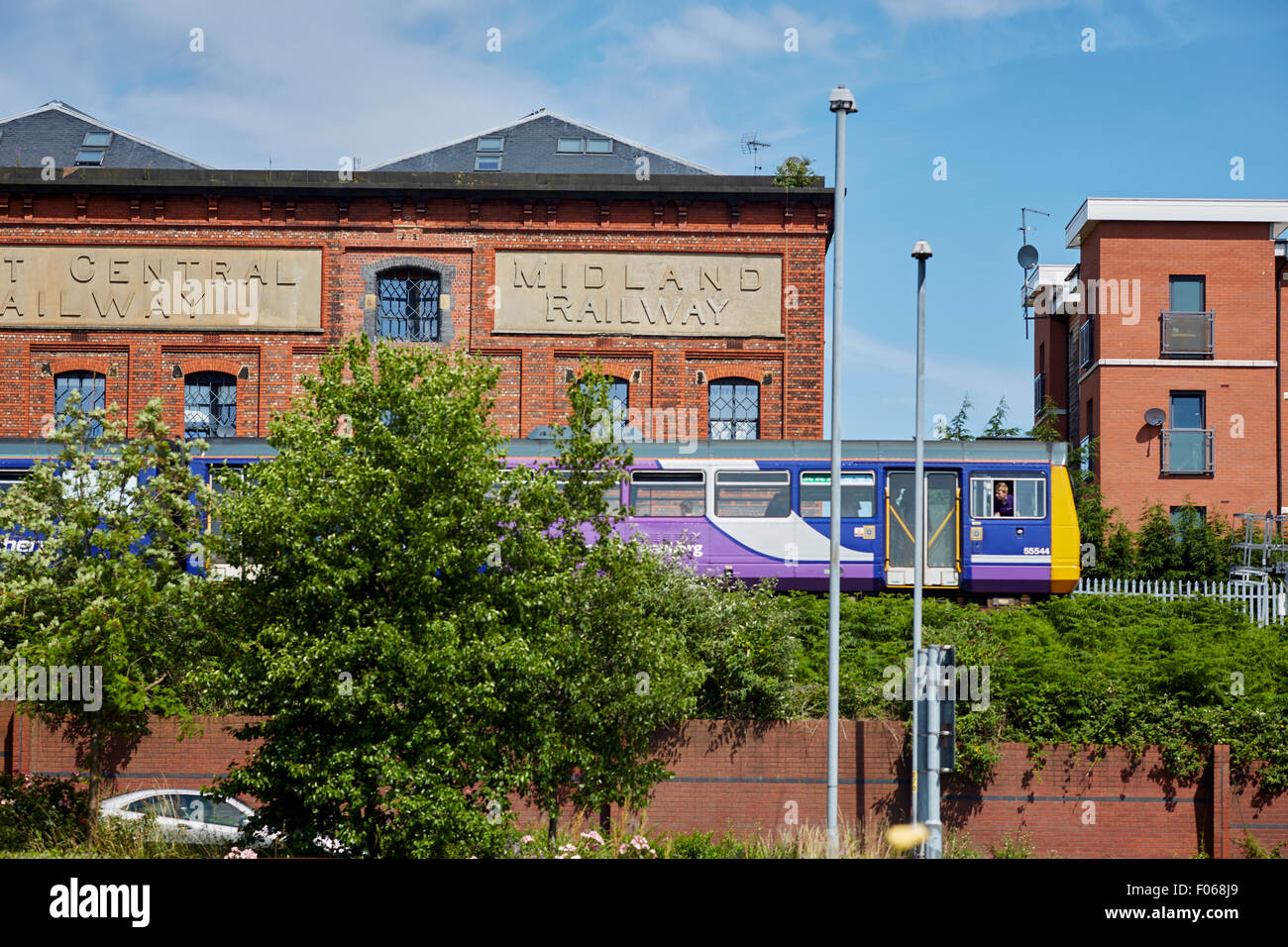 A Northern Rail 142 Pacer leaves Warrington Central with and old Midland Railway warehouse behind   Transport transporter - Stock Image