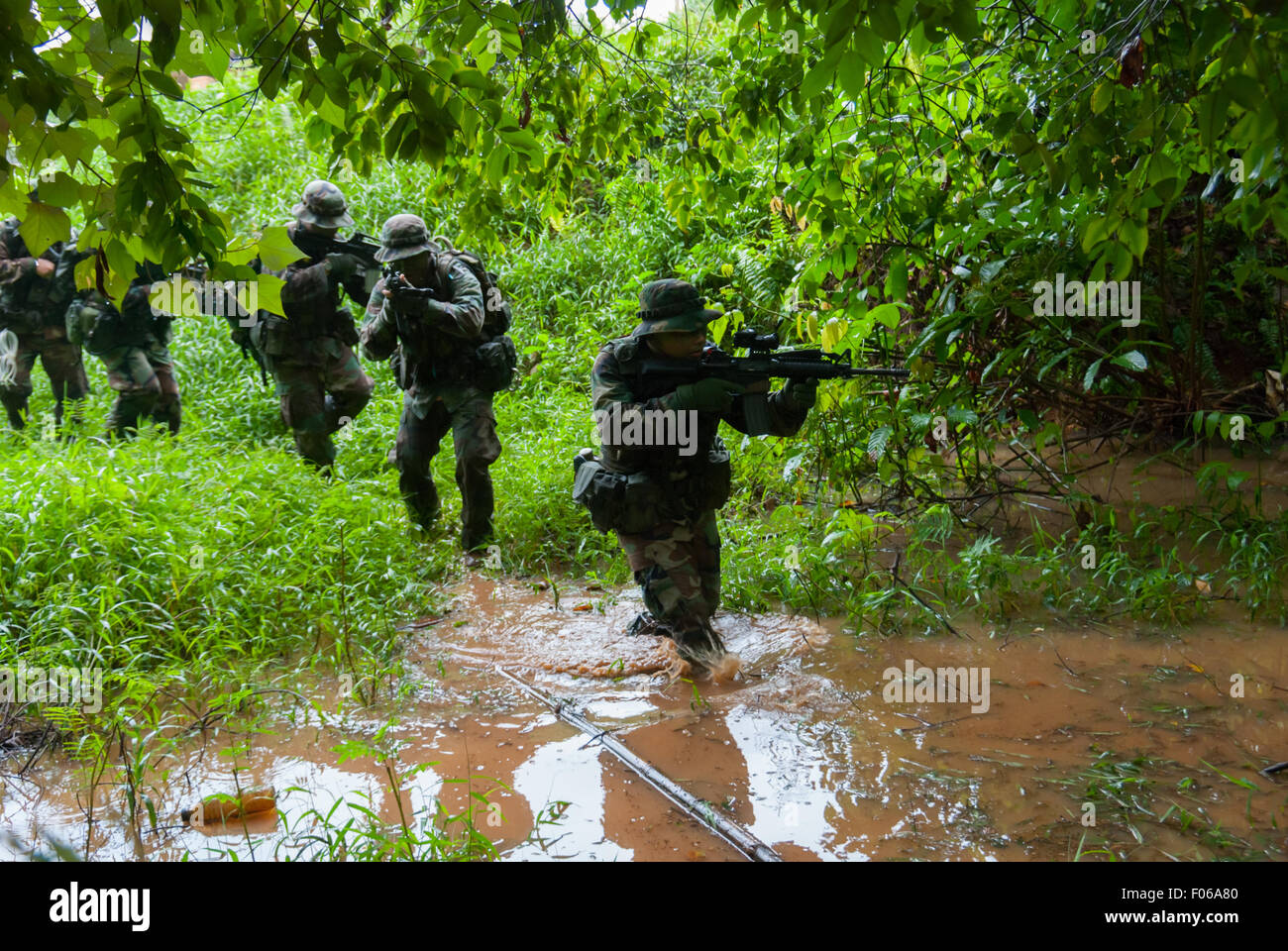 Men walking in swamp area during a recreational, military reenactment play. - Stock Image