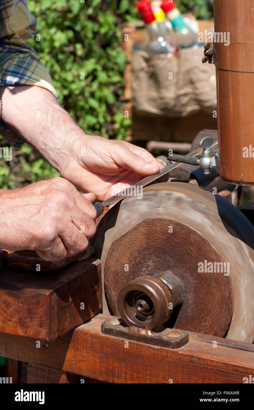 Italy, Lombardy, Knife Sharpener Grinding a Blade. - Stock Image