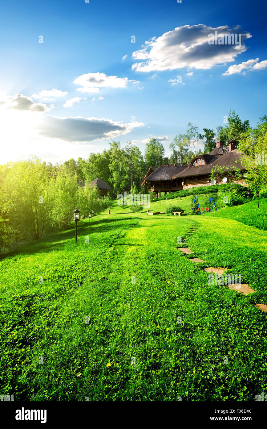 Wooden houses on green meadow in spring - Stock Image