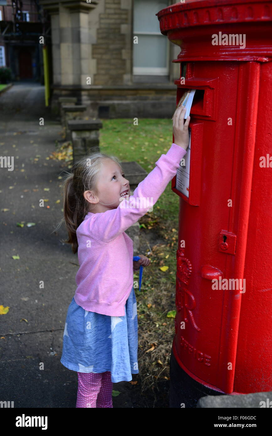 A little girl posting a postcard in York, North Yorkshire, UK. Picture: Scott Bairstow/Alamy - Stock Image