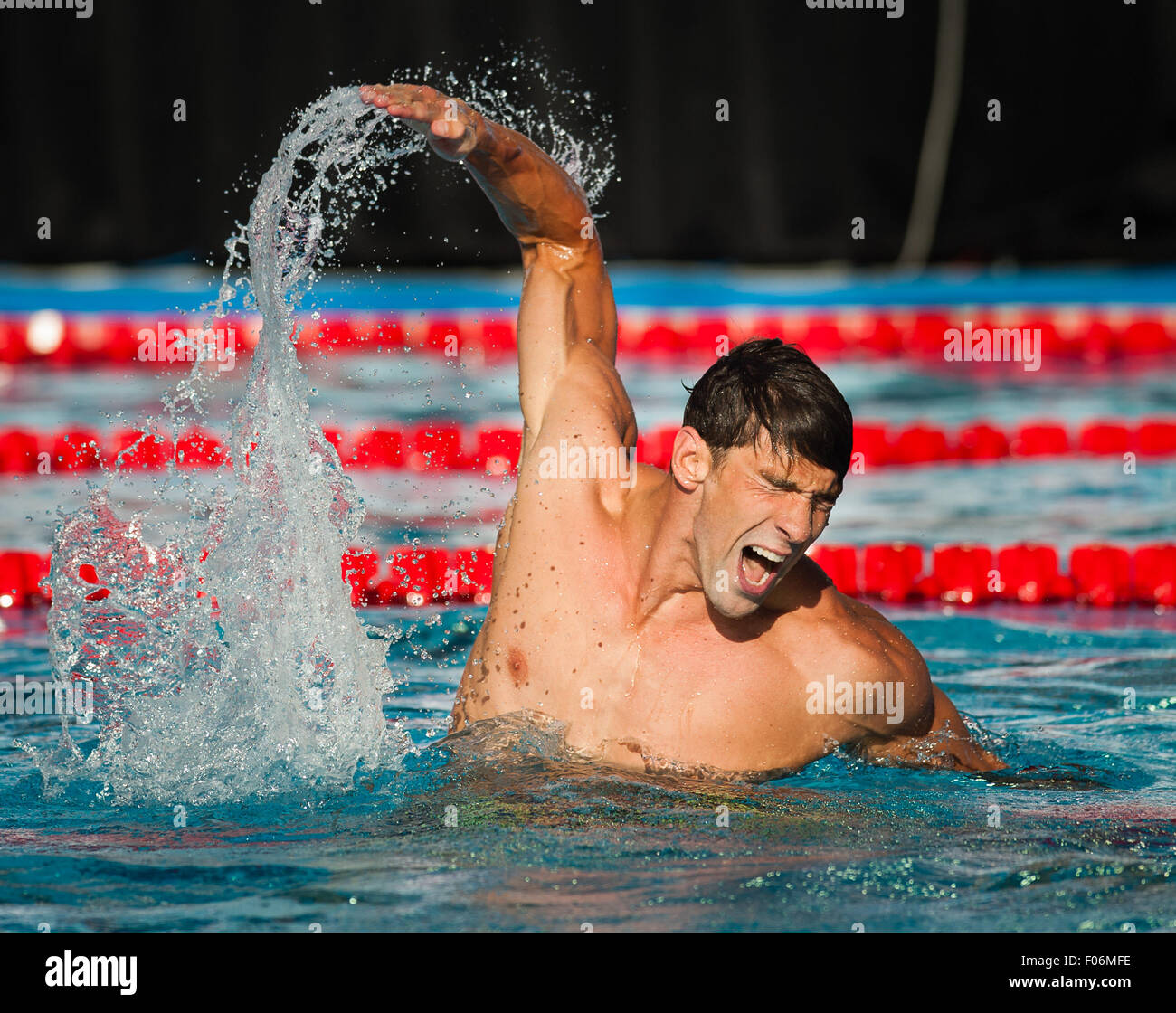 Michael Phelps reacts after winning the Final of the 100m Butterfly during the Phillips 66 National Swim Championships - Stock Image