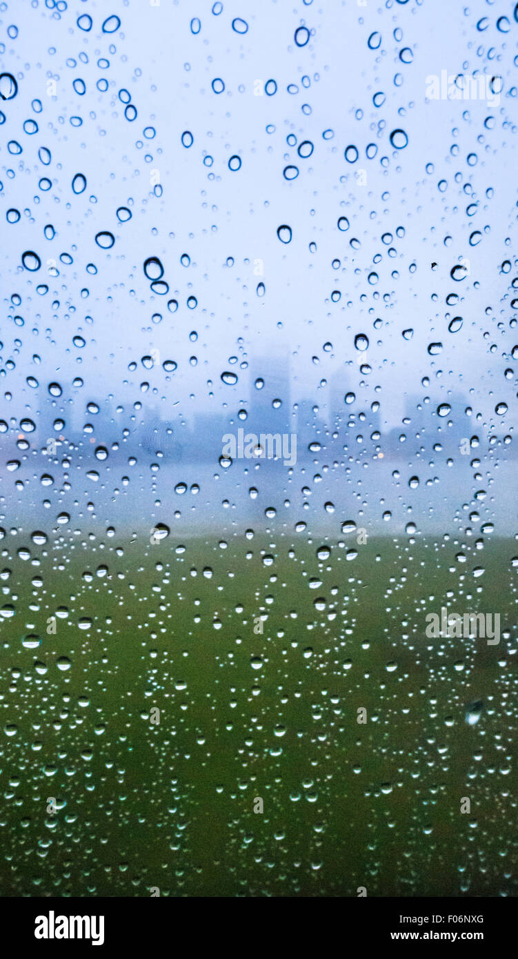 Droplets of rain on a window with the silhouette of a city in the background. - Stock Image