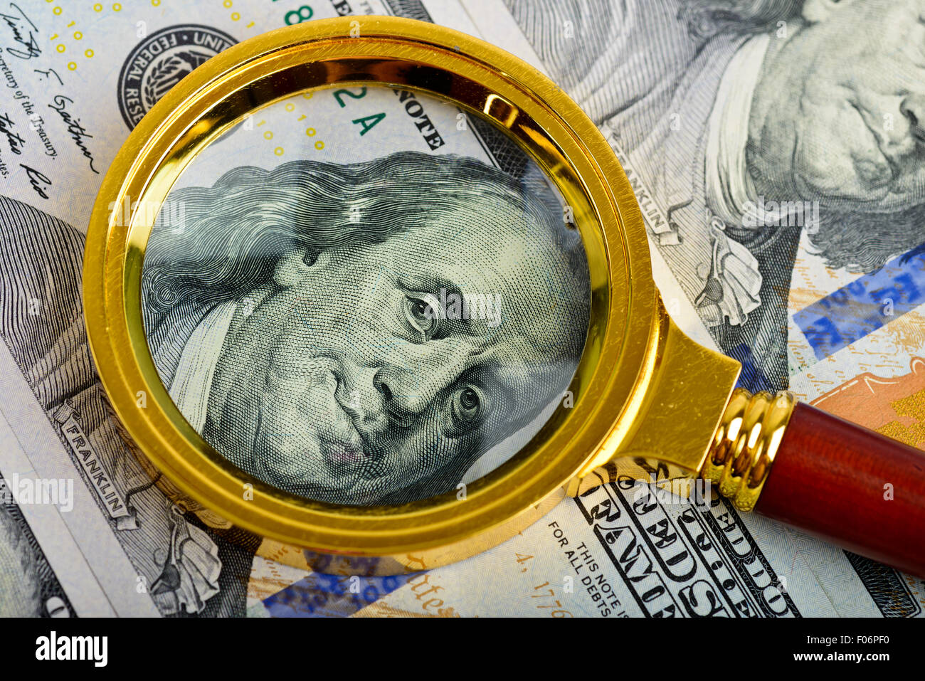 One hundred dollars banknotes with vintage magnifying glass - Stock Image
