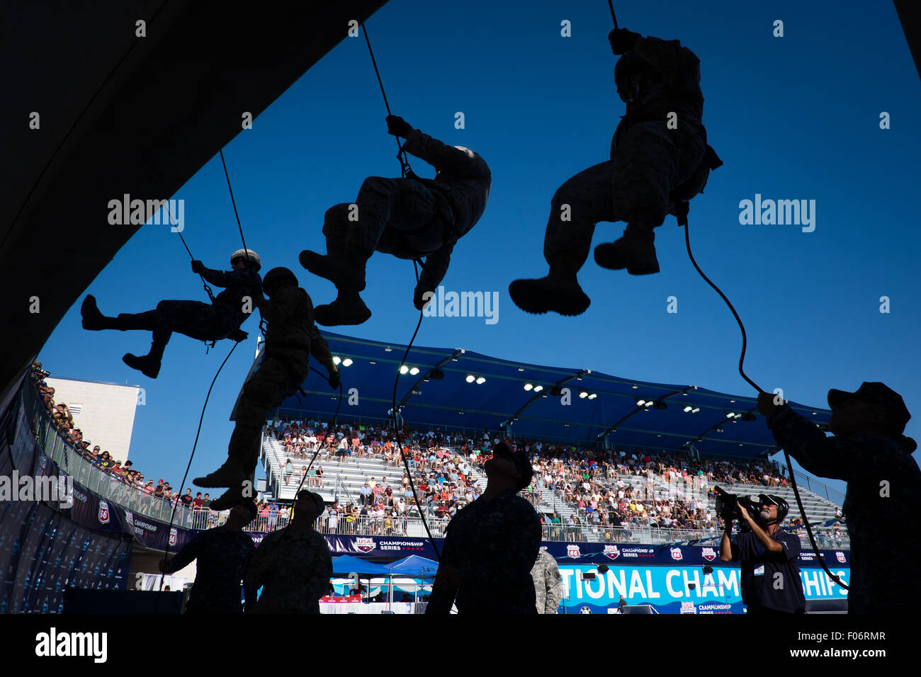 Military personnel rapel into the aquatic center during starting ceremonies of the Phillips 66 National Swim Championships - Stock Image