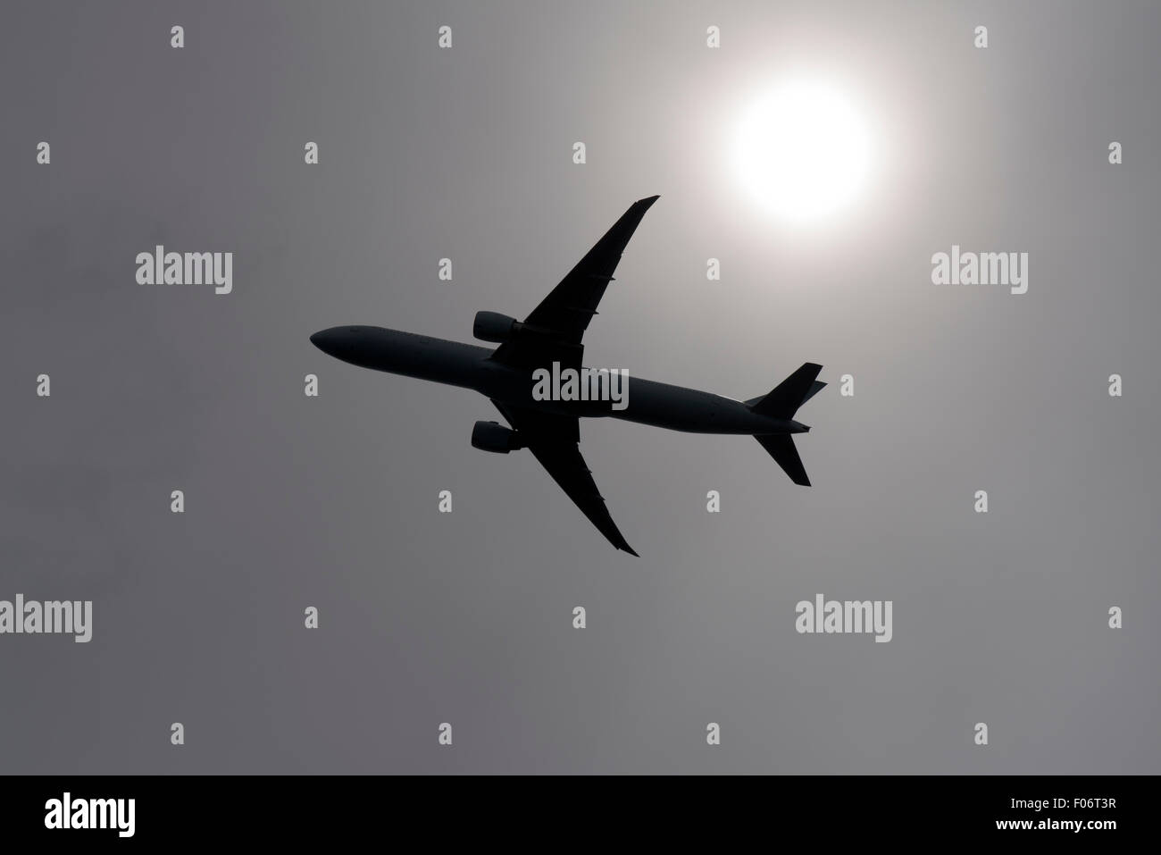 Commercial jet silhouetted by the sun shining through high overcast - Stock Image