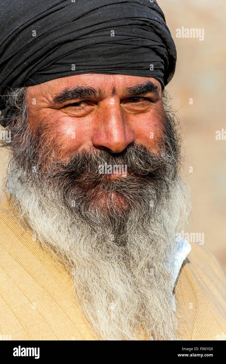 Punjabi man smiling with black turban and a wonderful greying beard - Stock Image
