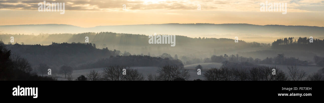 Low morning winter sun rises over the misty landscape as viewed from Newlands Corner, Guildford, Surrey Stock Photo