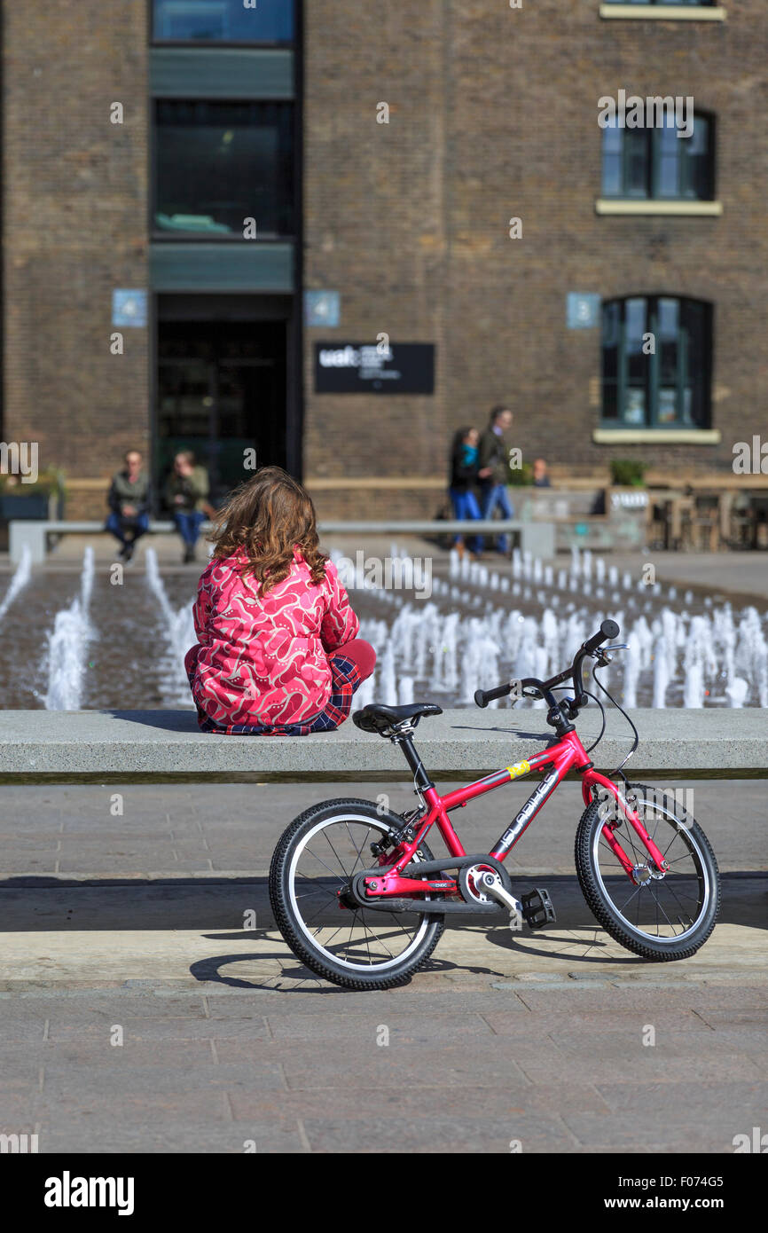 A young girl sits by her bicycle watching the 'Granary Squirt' fountain at Granary Square, King's Cross, - Stock Image