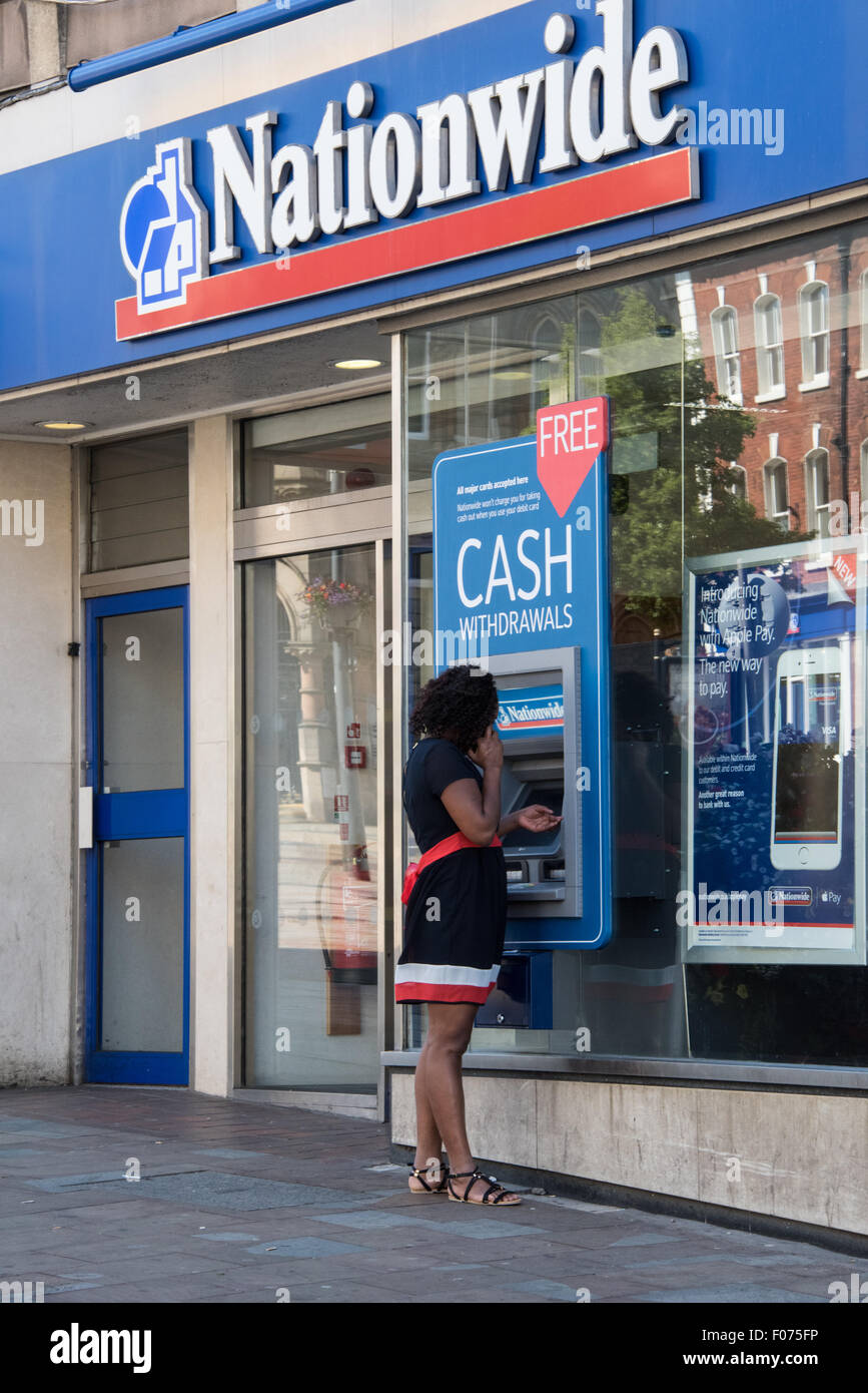 A woman on her phone and using the ATM at Nationwide Bank on