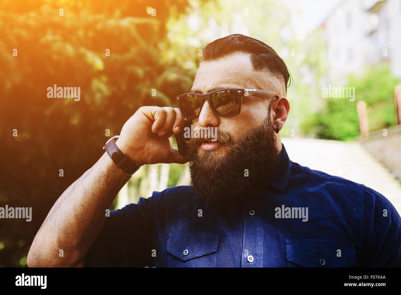 bearded speaks by phone - Stock Image