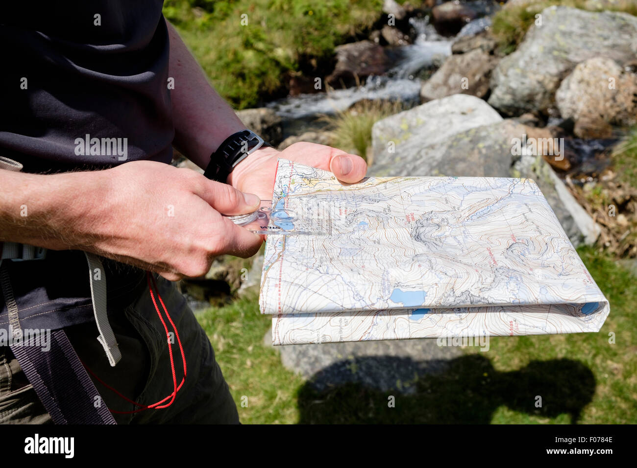 Hiker holding a hiking map and using a navigation compass to measure distance navigating on a hike in Snowdonia - Stock Image