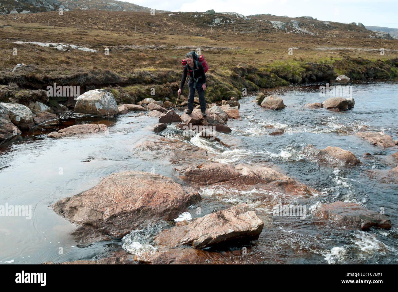Walker crossing the Strath Cailleach river, near Sandwood Bay, Cape Wrath wilderness, Sutherland, Scotland, UK - Stock Image