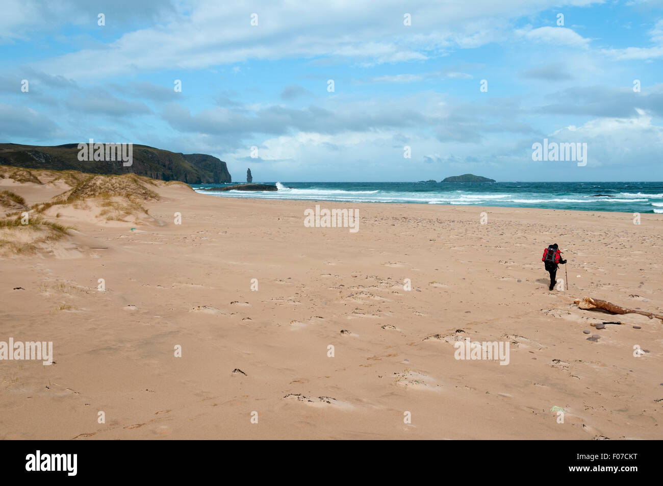 A walker on the beach at Sandwood Bay with the Am Buachaille sea stack in the distance.  Sutherland, Scotland, UK - Stock Image