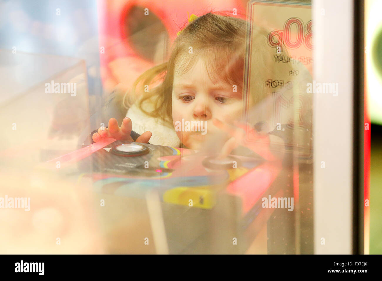 A child playing on a amusement arcade machine - Stock Image