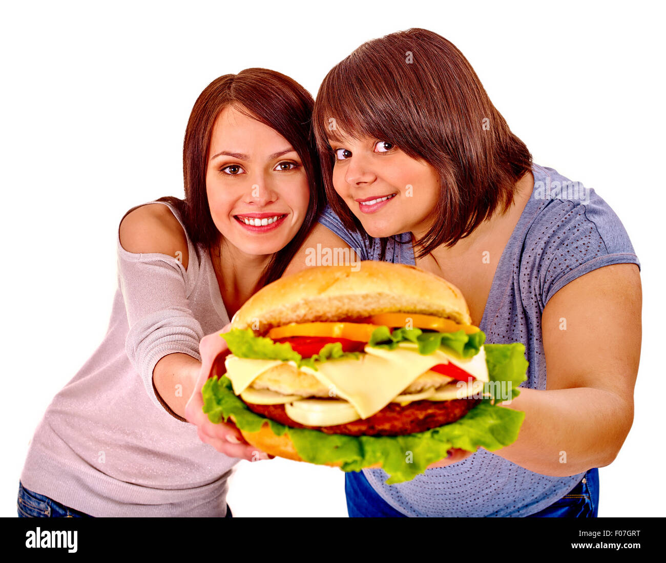 Women eating hamburger. - Stock Image