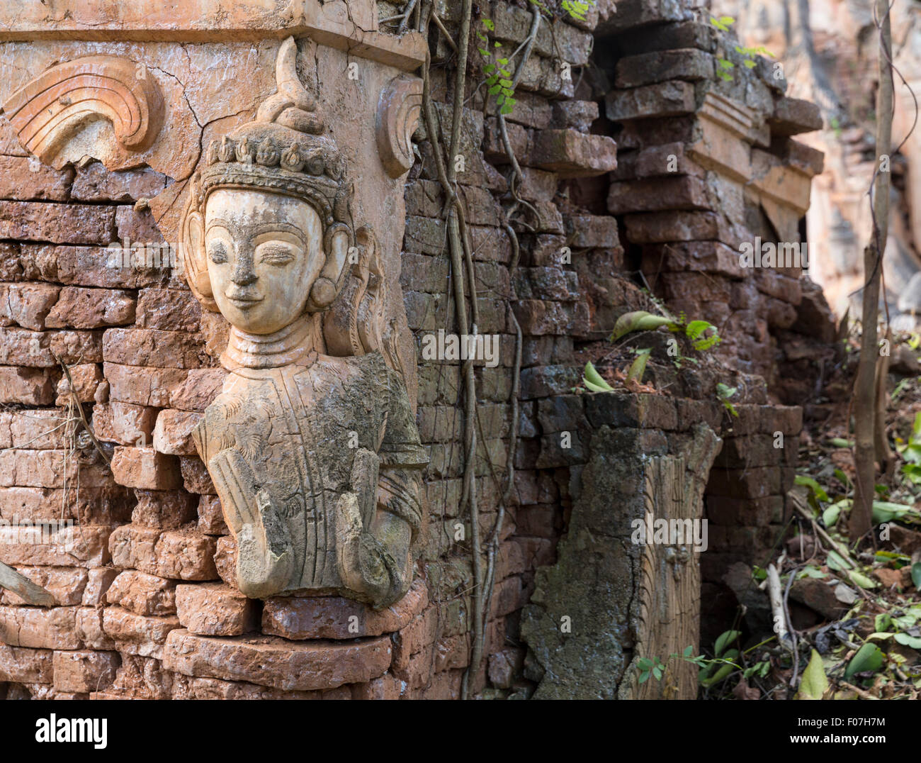 Overgrown 12th century brick stupas and statue in Nyaung Ohak section of the ruins at Indein, Inle Lake, Shan State, - Stock Image