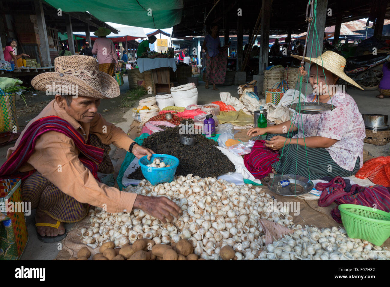 Garlic vendors at the Nam Pan 5 day market on Inle Lake in Myanmar. The market rotates between villages on a 5 day - Stock Image