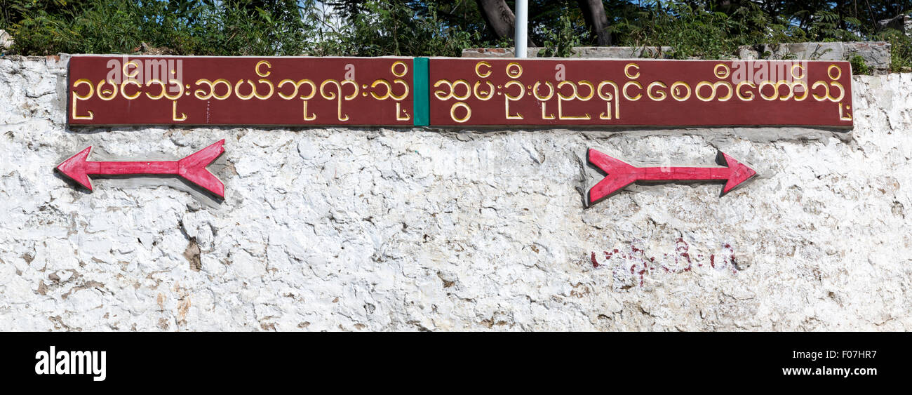Road signs in Burmese script with arrows pointing to pagodas in either direction.in Sagaing, Myanmar. Confused? - Stock Image