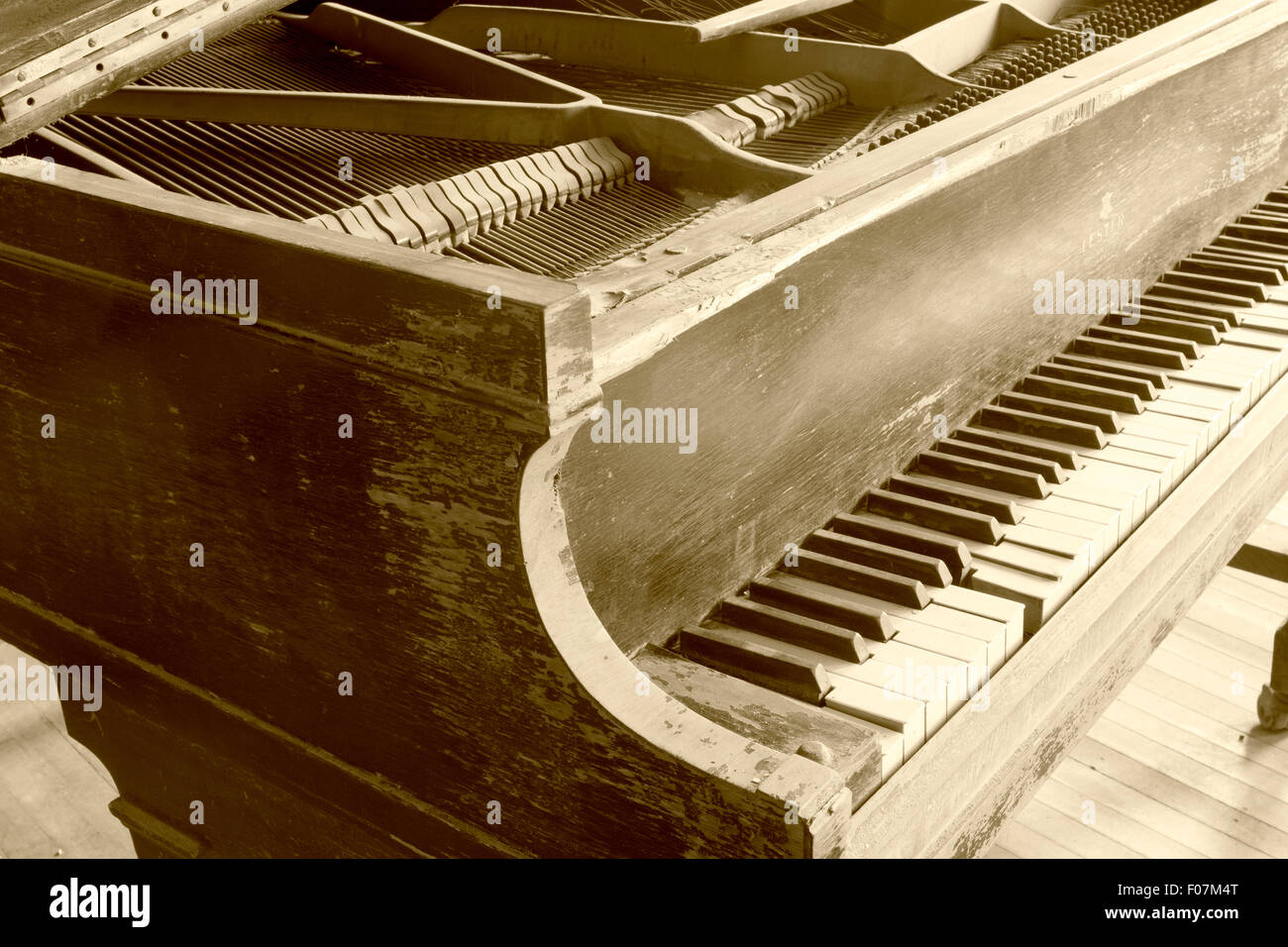 Wooden piano keyboard in sepia tones. - Stock Image