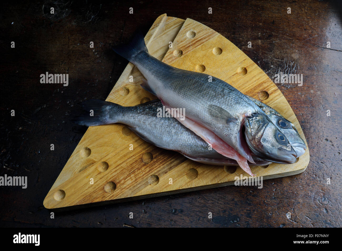 uncoucked fish on an old brown table Stock Photo