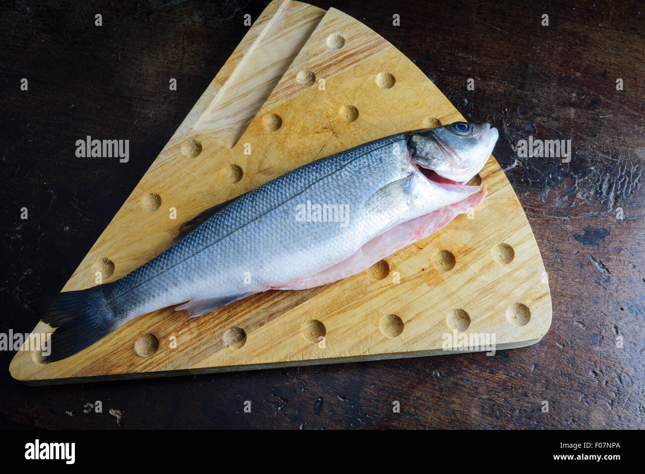 uncoucked fish on an old brown table - Stock Image