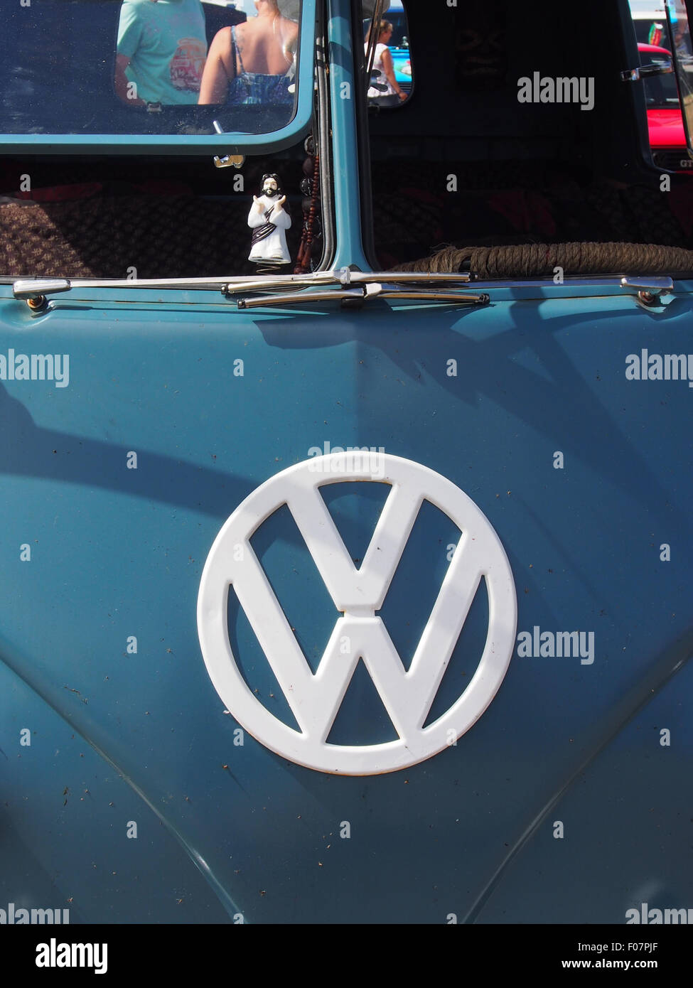A VW emblem on the front of a classic VW campervan. The windows are open with a buddy Christ in the window - Stock Image