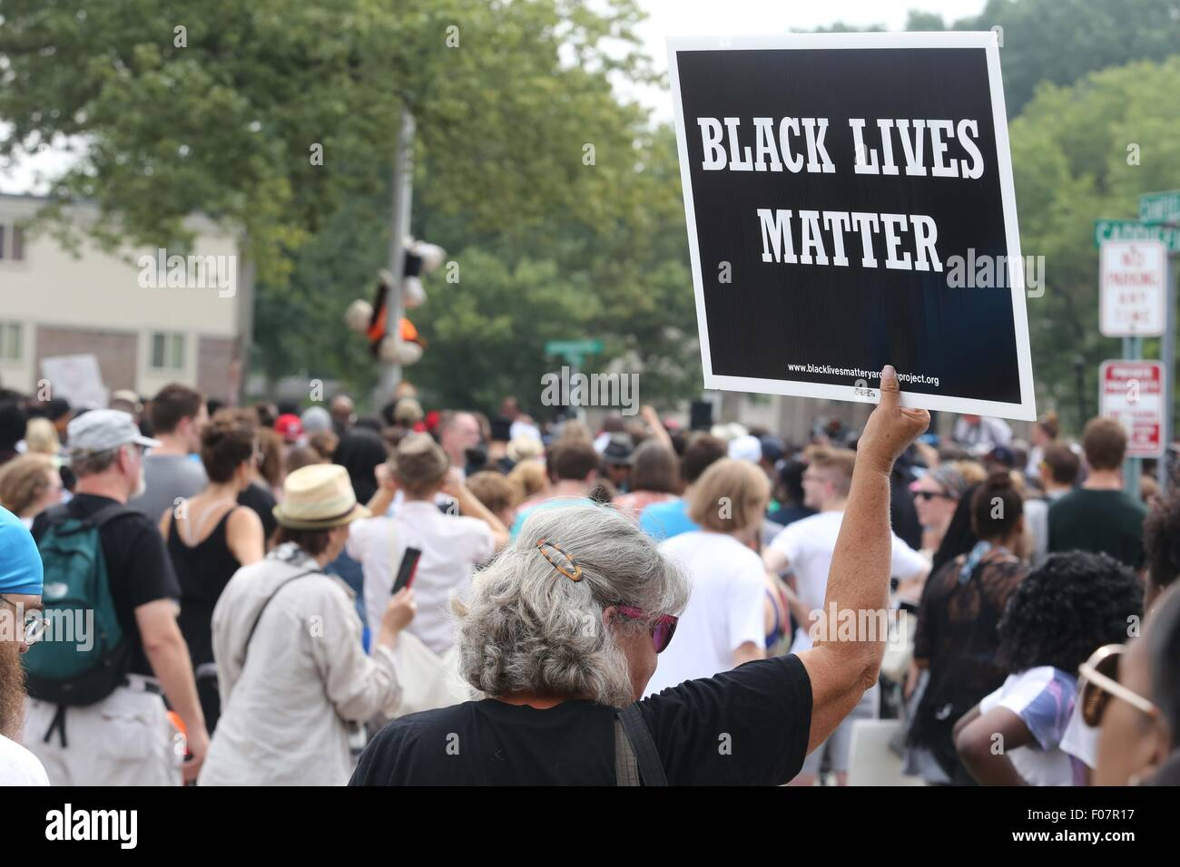 Ferguson, Missouri, USA. 9th Aug, 2015. A woman holds up a Black Lives Matter sign at the Michael Brown memorial - Stock Image