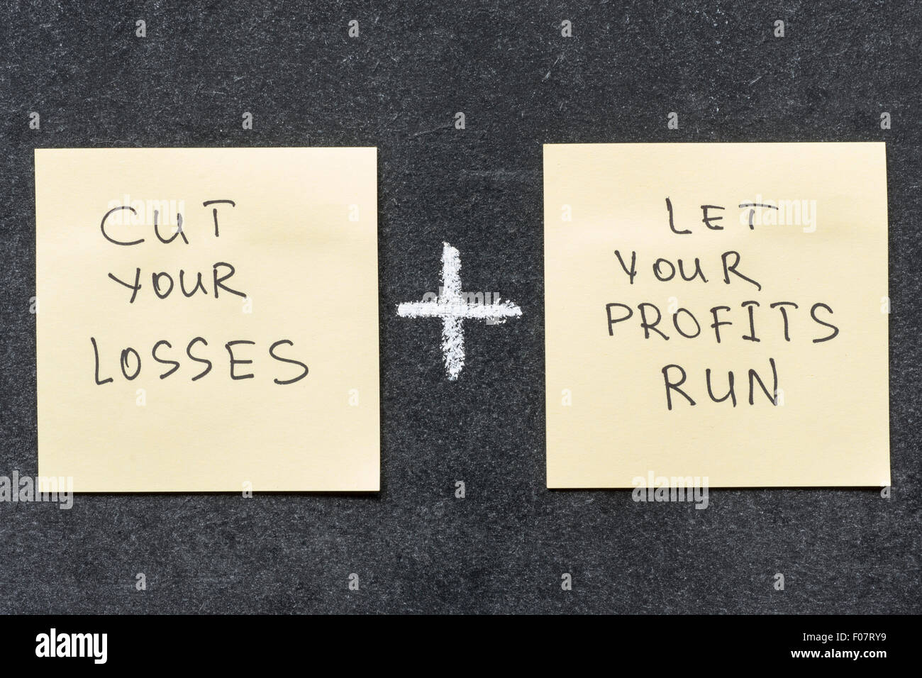 cut your losses and let your profits run proverb interpretation handwritten on sticker notes - Stock Image