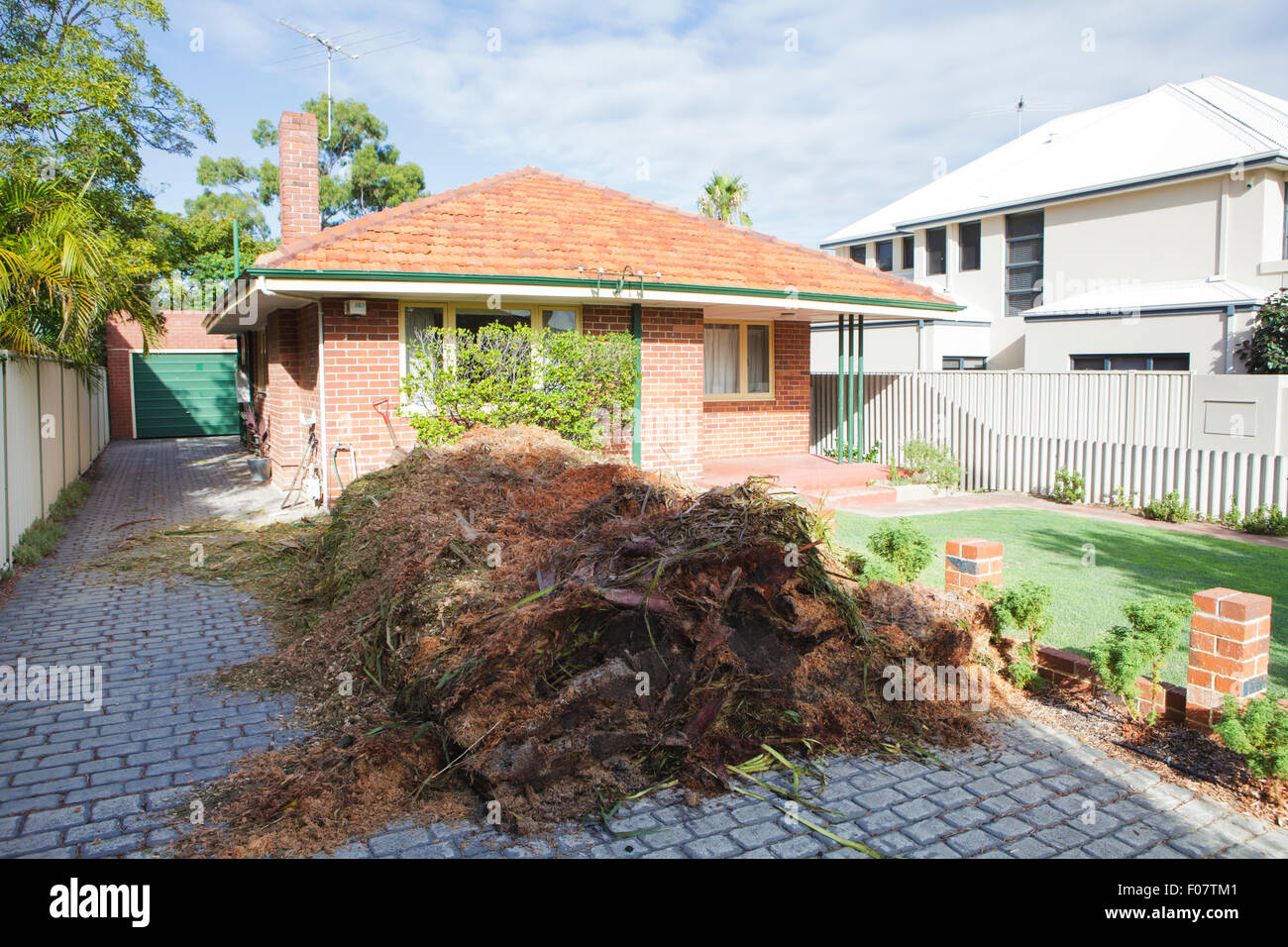 A large pile of mulch on a driveway. - Stock Image
