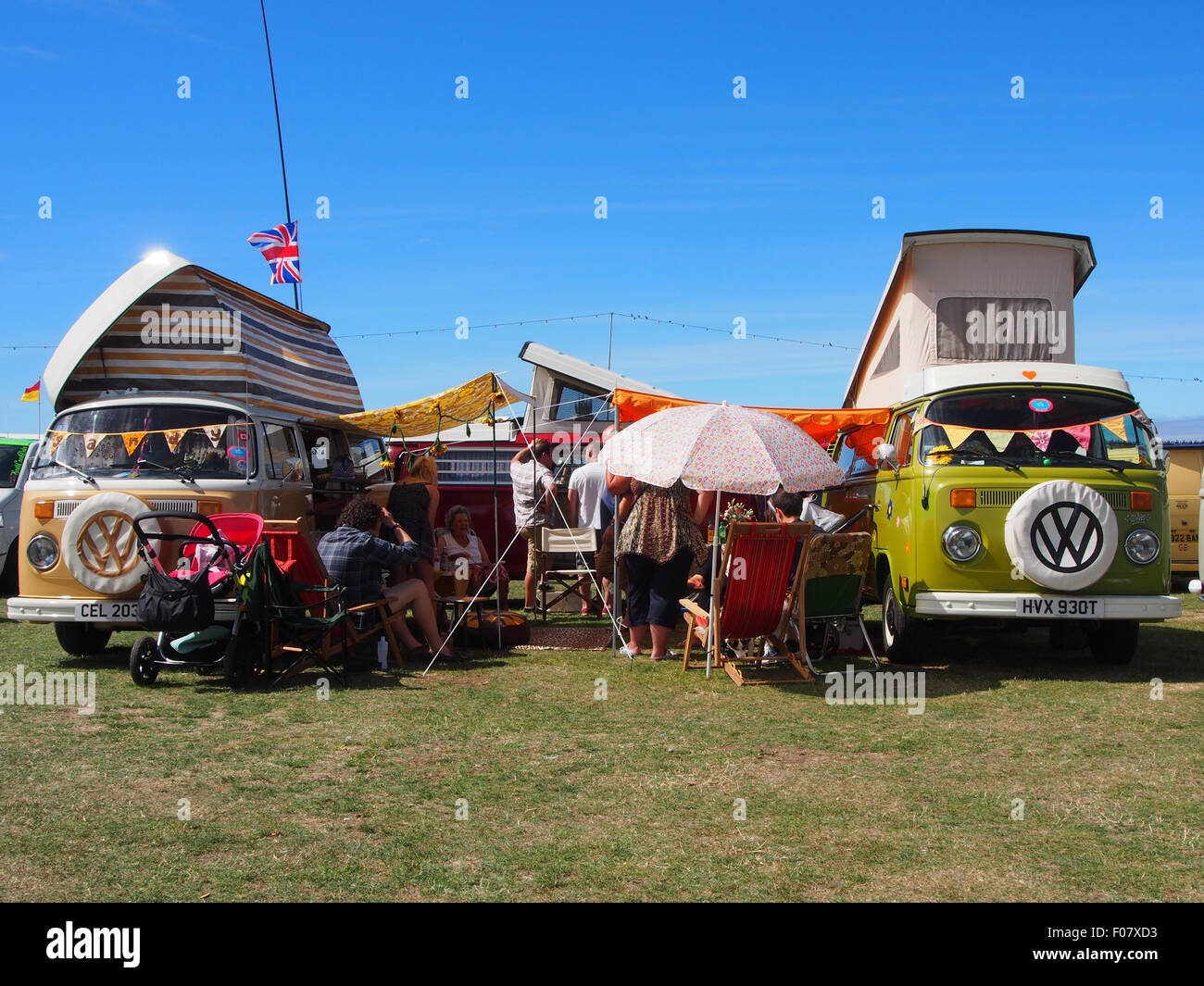 People camping outside two classic VW campervans in a field - Stock Image