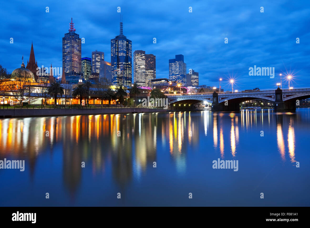 The skyline of Melbourne, Australia with Flinders Street Station and the Princes Bridge from across the Yarra River at night. Stock Photo