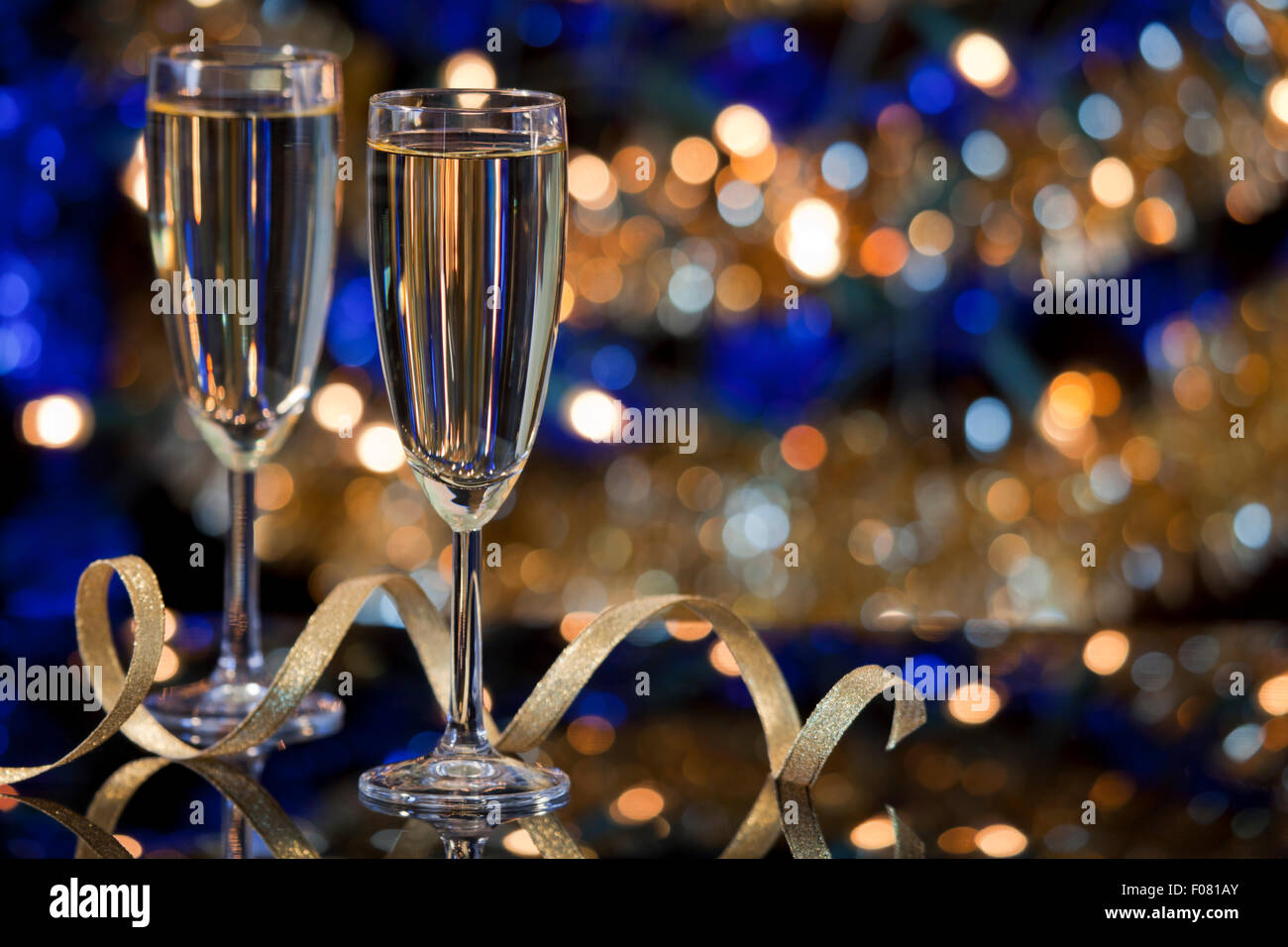 a new years eve scene with champagne glasses and christmas lights in the background