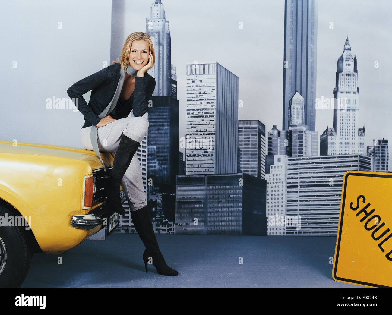 4ee00adbb0d Happy blonde woman wearing casuals and long boots sitting on hood of car,  smiling