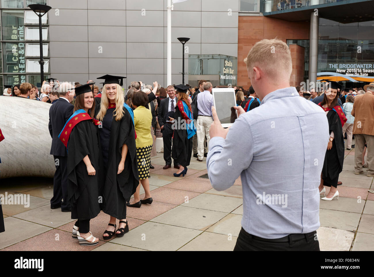 man using tablet computer to take photos of female graduates after manchester metropolitan university graduation - Stock Image