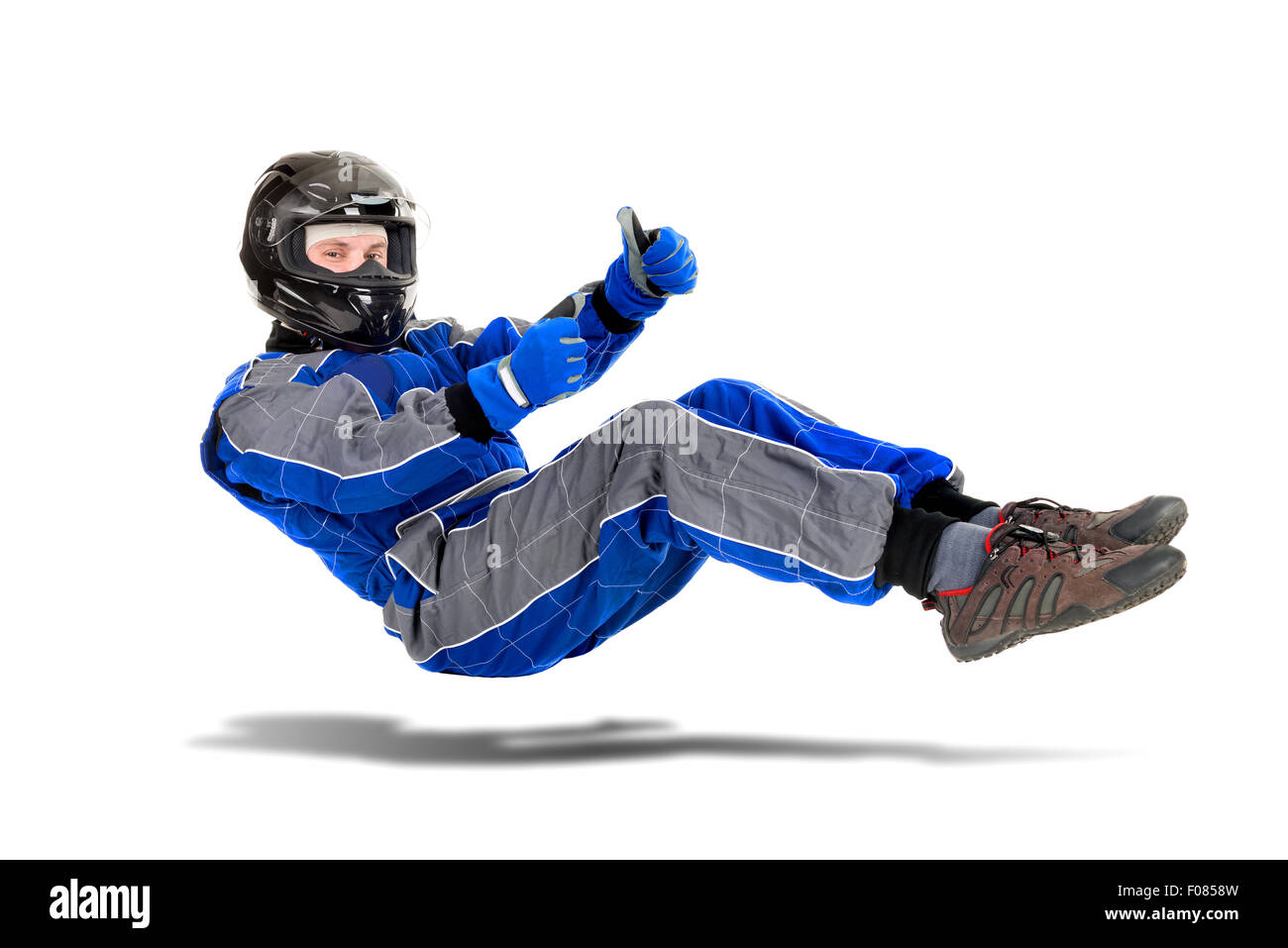 Racing driver posing in driving position in full gear isolated in white - Stock Image