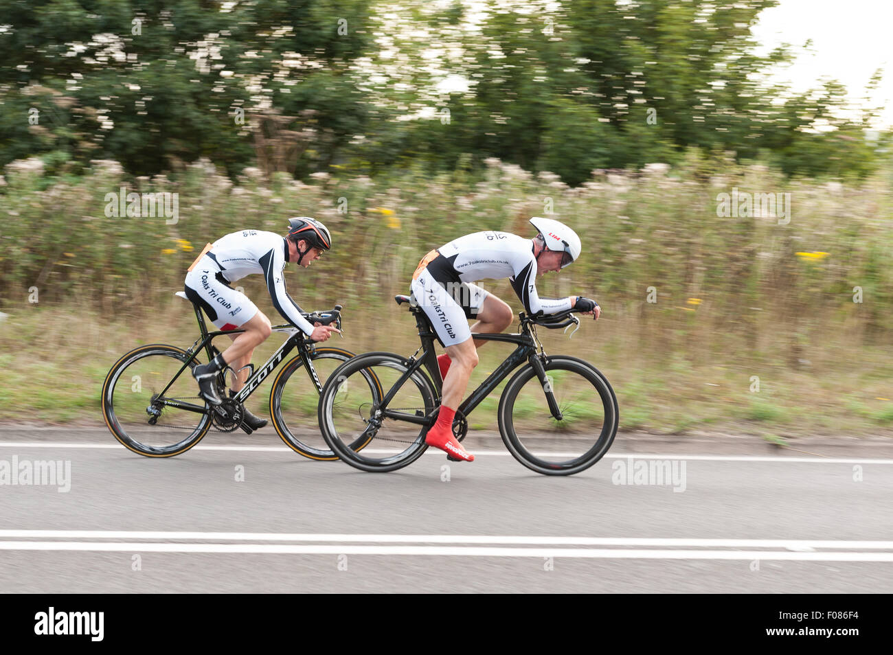 TT time trial cycling pairs on Brands Hatch road dedicated gear equipment bikes and streamlined on very fast road summer evening Stock Photo