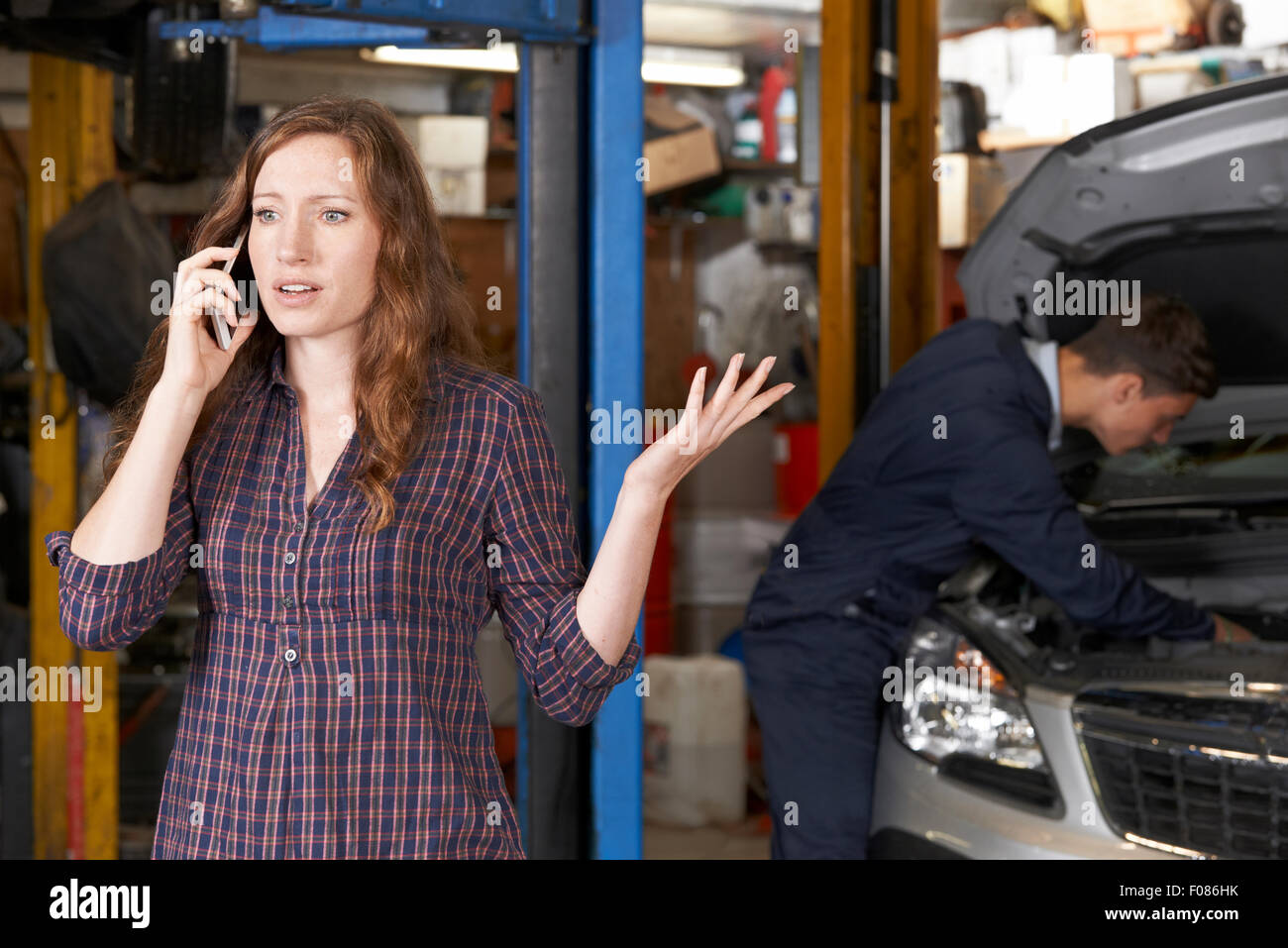 Frustrated Female Customer On Mobile Phone At Auto Repair Shop - Stock Image