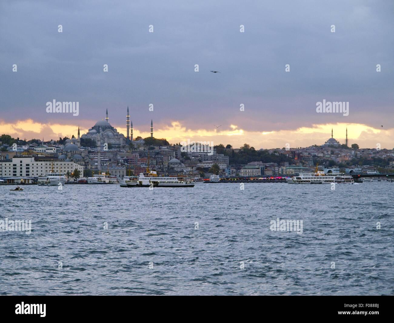 View of cityscape of city on coast of Bosphorus and ferryboats at dusk, Istanbul, Turkey - Stock Image