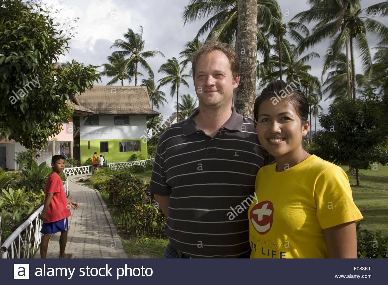 Jorg Thiemann with Azubine standing on pavement of Beluga School for Life, Thailand - Stock Image