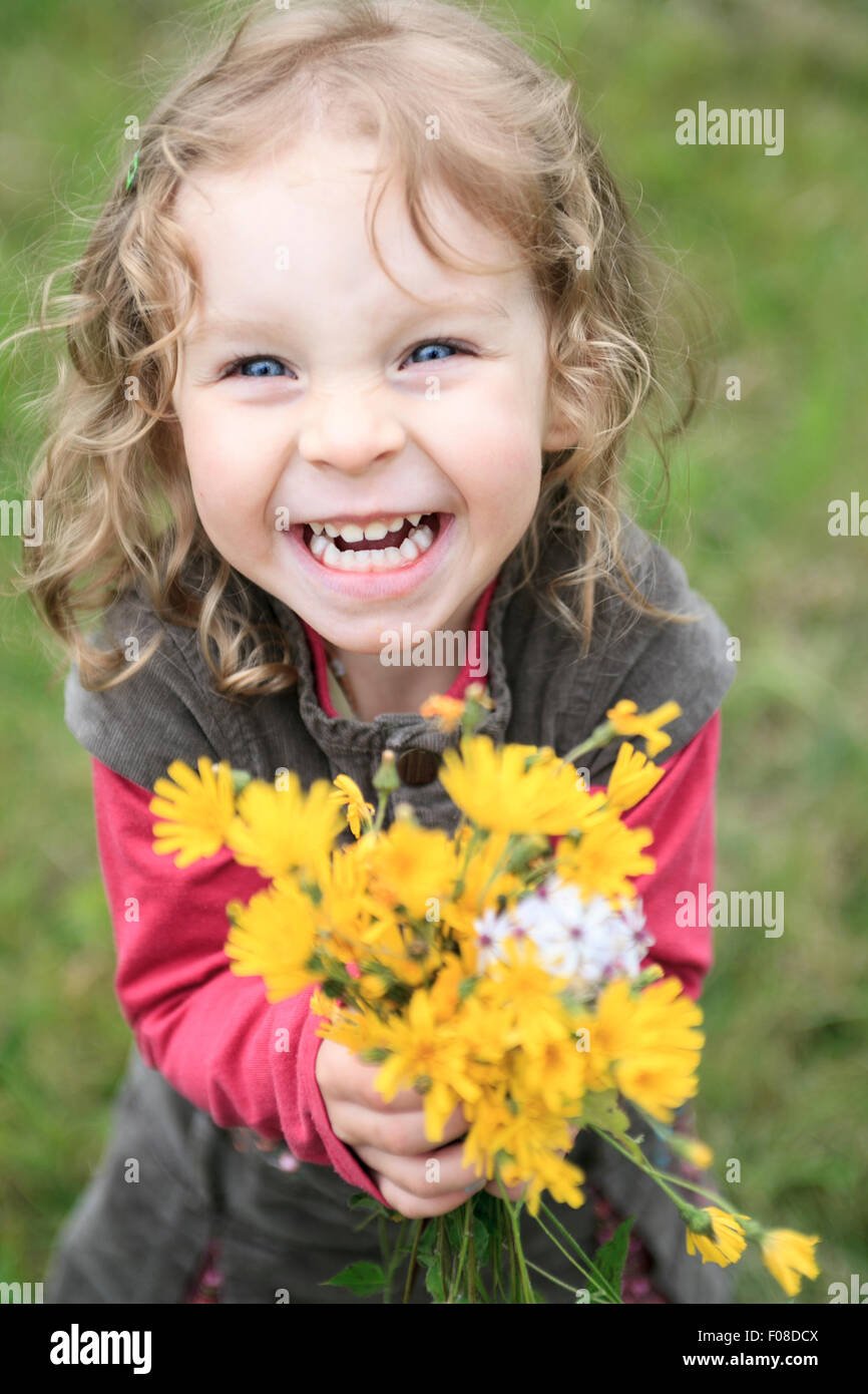 happy baby girl playing outdoor, cute child holding fresh flower