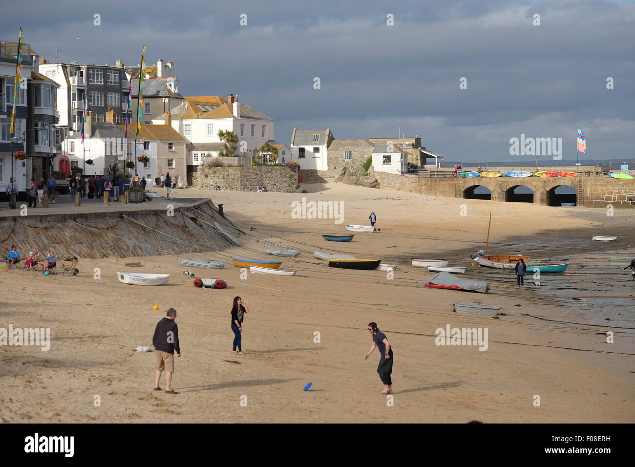 St Ives, Cornwall, UK:  Three family members playing Frisbee on the beach in the late afternoon sun - Stock Image
