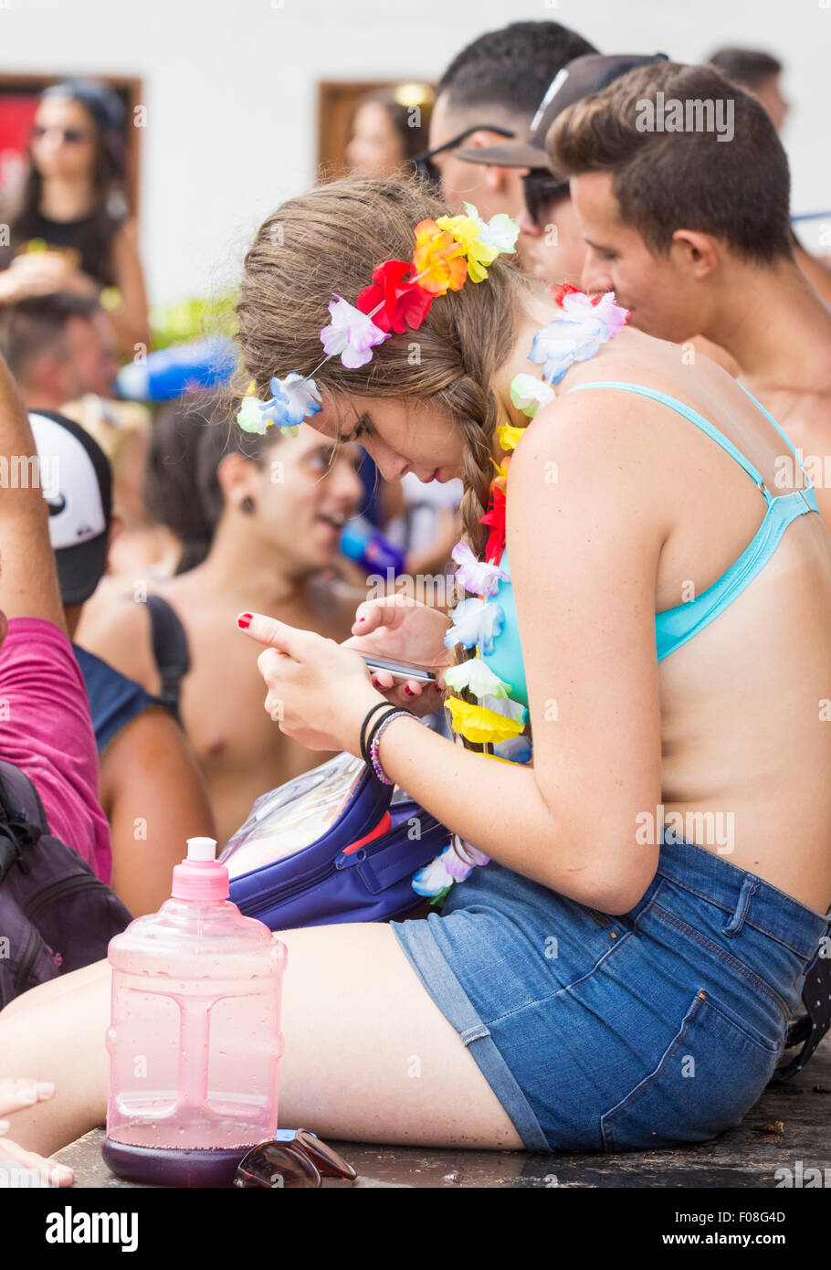 Young woman using mobile phone at festival, oblivious to the loud music and crowds of people. - Stock Image