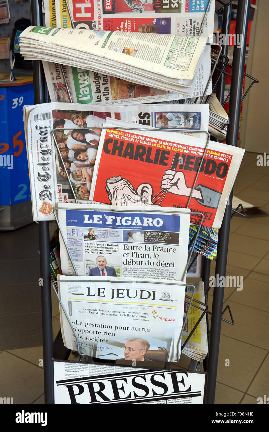 Satirical weekly news magazine Charlie Hebdo between international newspapers at a sale diplay in a store in Luxembourg - Stock Image