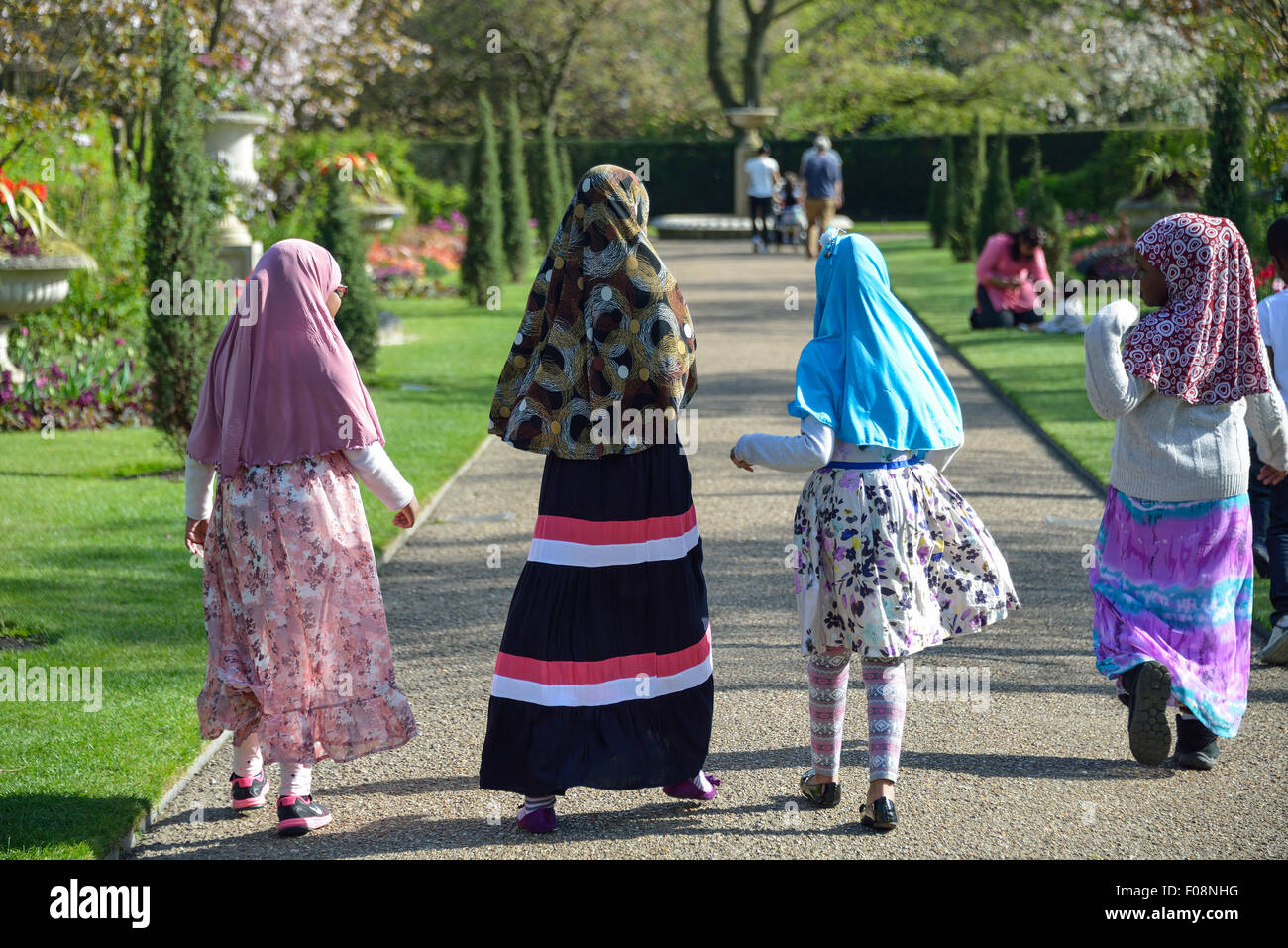 Young Muslim school girls in Queen Mary's Gardens, Regent's Park, London Borough of Camden, London, England, United Stock Photo