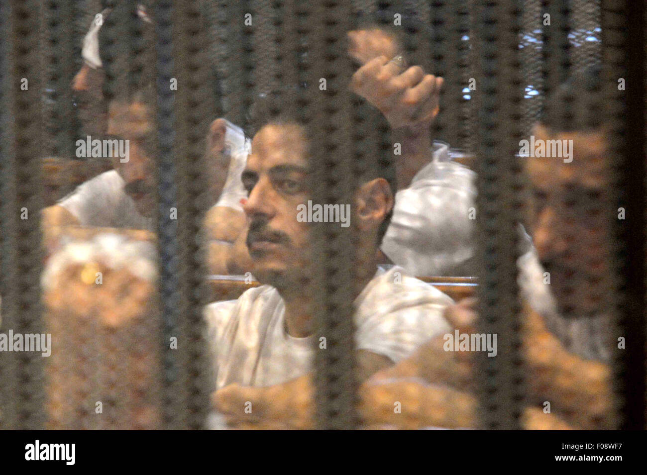 Cairo, Egypt. 9th Aug, 2015. Egyptian defendants sit behind bars during their trial over a 2012 stadium riot in Stock Photo
