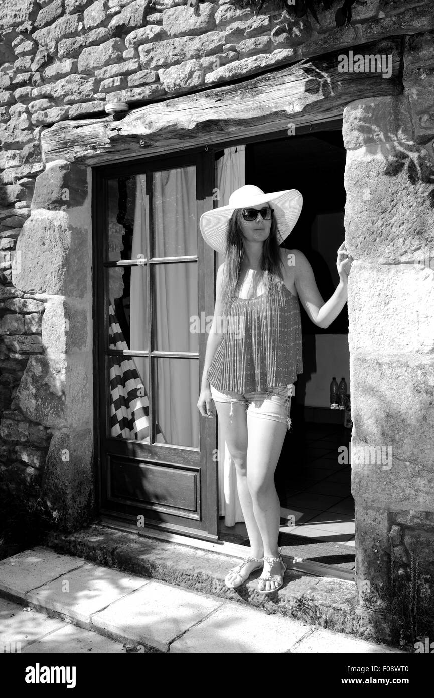 Young beautiful woman in her 20s wearing large brimmed sun outside her holiday gite in France Lot Region - Stock Image