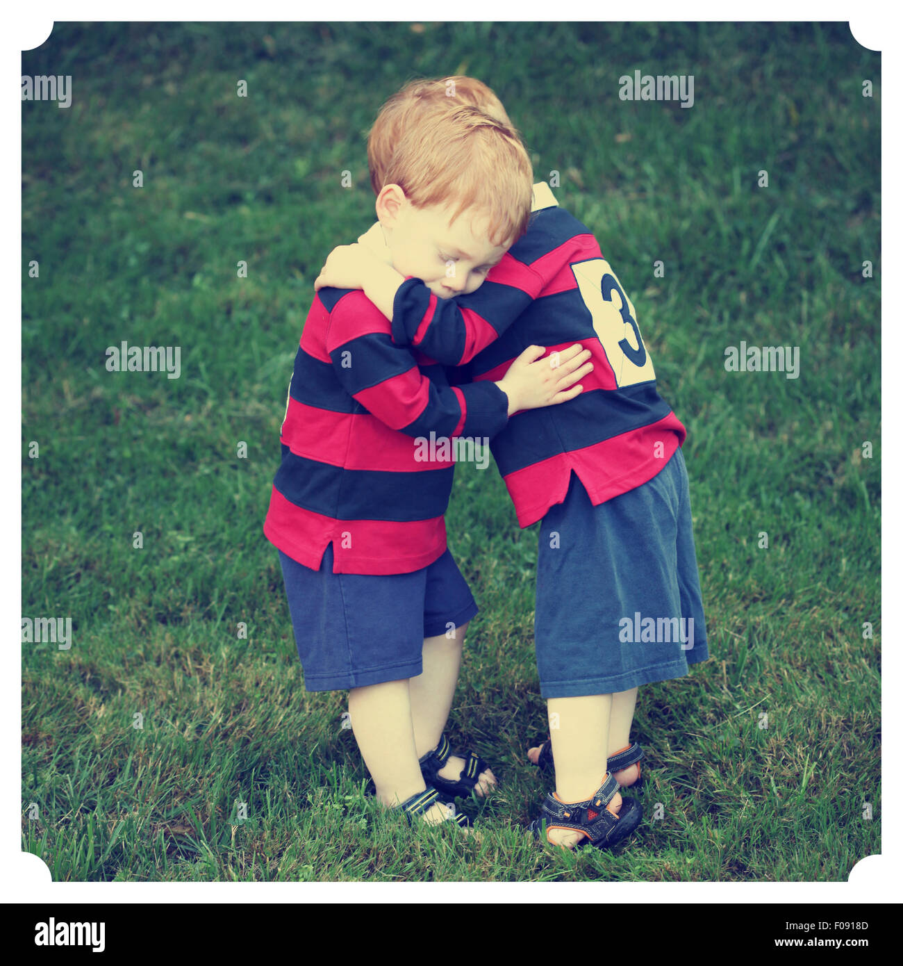 Twin baby boys hugging in rugby clothing with Instagram effect filter - Stock Image